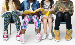 deDiverse group of kids sitting in a row reading books