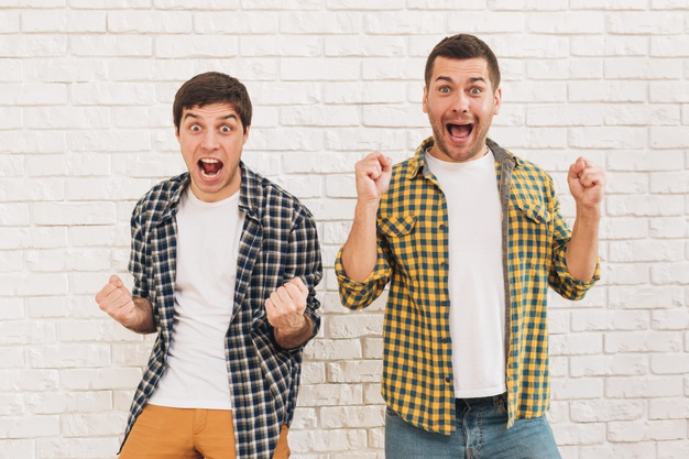 excited-young-male-friends-standing-against-white-brick-wall-clenching-their-fist_23-2148160182