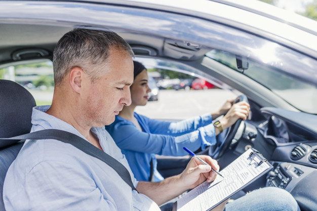 Instructor of adriving school giving exam while sitting in car.