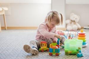 cute-girl-sitting-carpet-playing_23-2147663655