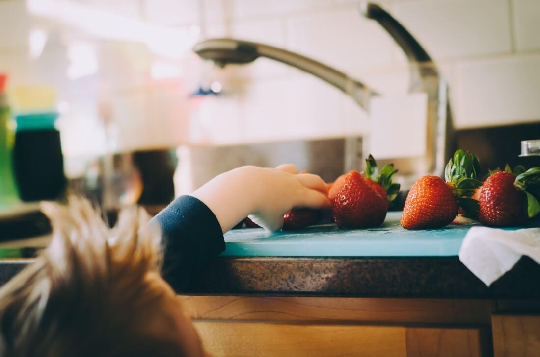 Dete uzima jagode sa sudopere