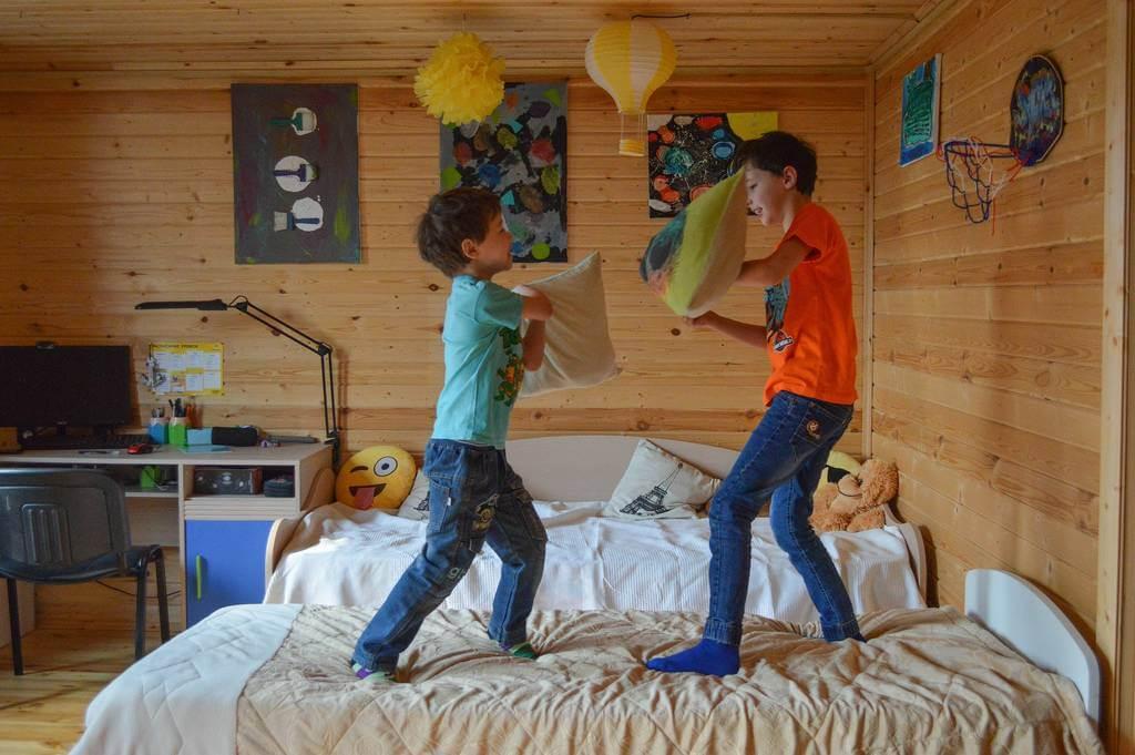 Deca se igraju na krevetu jastucima